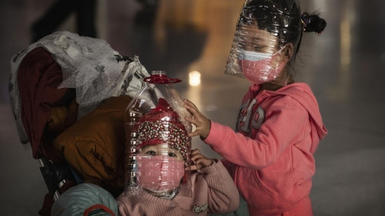 Chinese children wear plastic bottles as protective masks while waiting to check in to a flight in Beijing